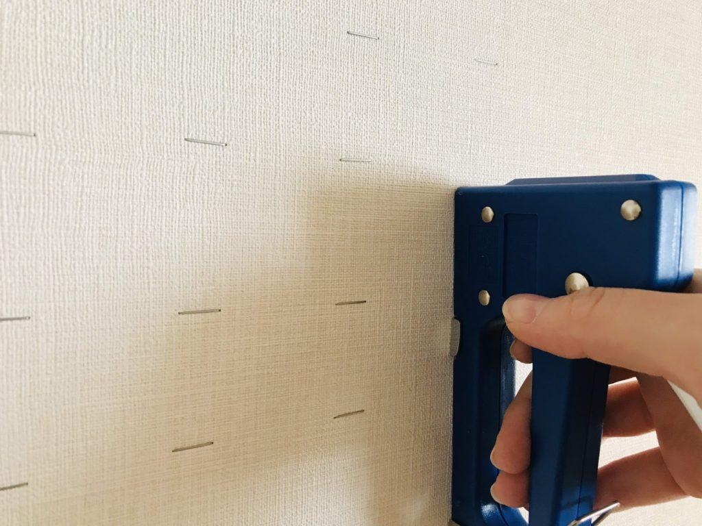 タッカーを壁に押し当てている図