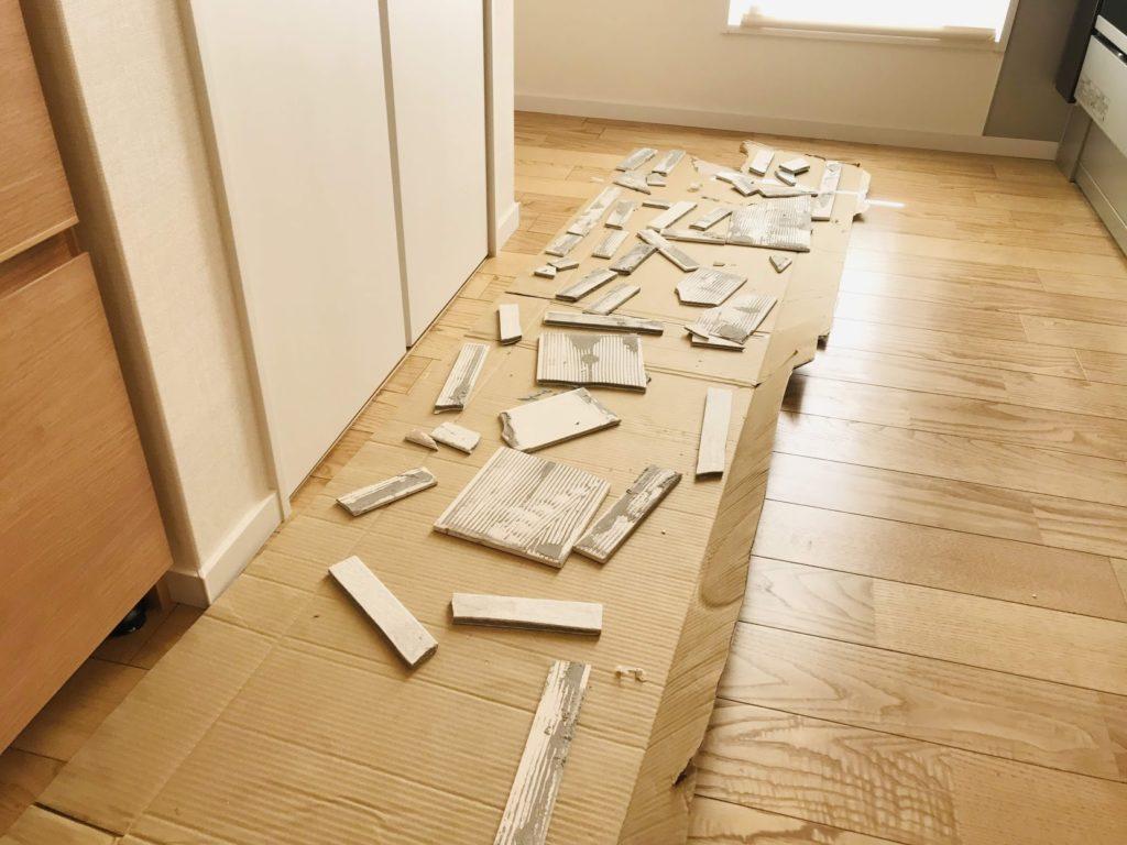 エコカラットの残骸を床に敷いた段ボールに並べている図